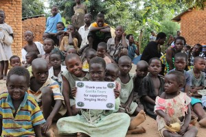 Children at Nakisenyi village with Gorilla Tours sign
